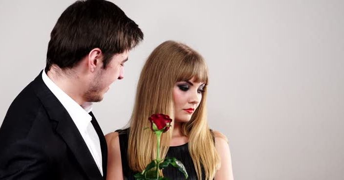 woman showing a lack on interest in a man with a rose