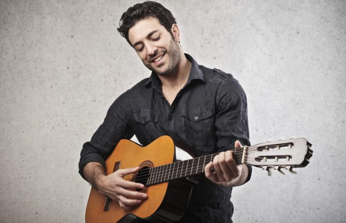 man playing the guitar on a grey background