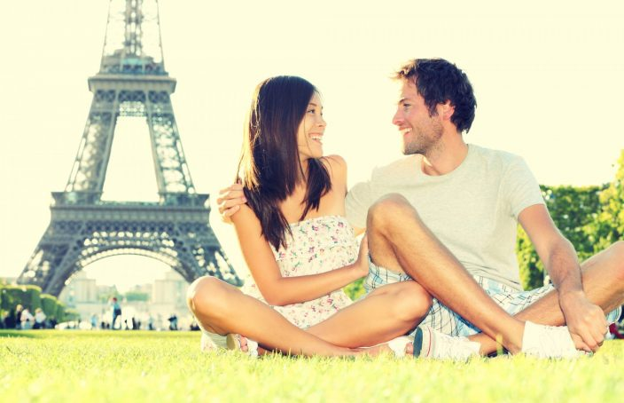 man and woman sitting in front of the eiffel tower