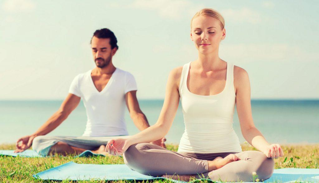 man and woman doing yoga outside