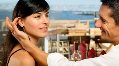 man placing woman's hair behind her ears