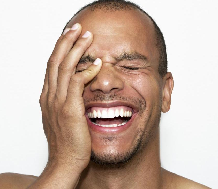 man laughing with his hand to his face