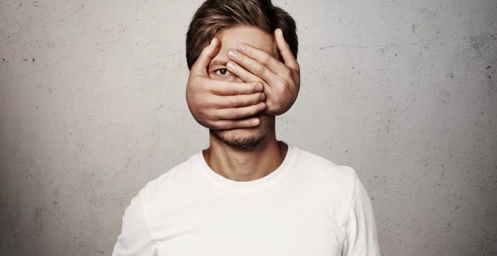 man with hands covering his face except his right eye