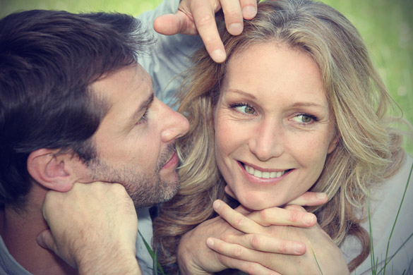 close up of a man moving the hair out of woman's face