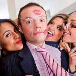 women surrounding a man trying to kiss him