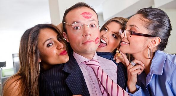 women surrounding a man trying to kiss him