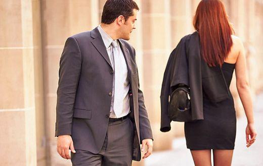 man looking at redhead woman as she walks away