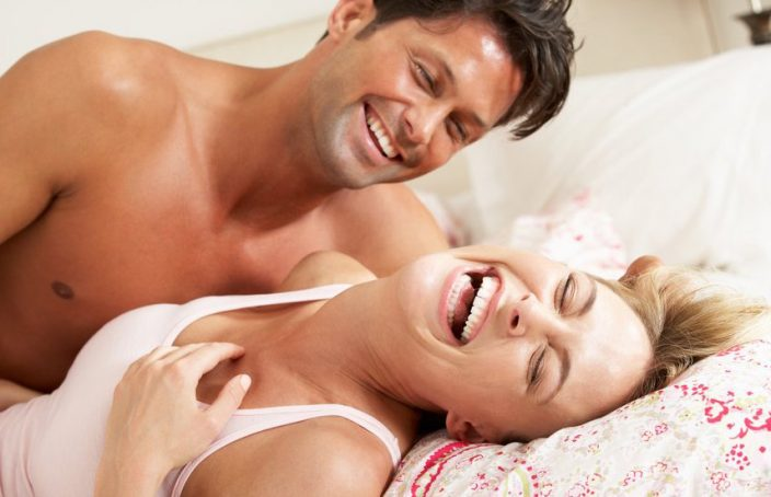 Man and woman laughing on bed
